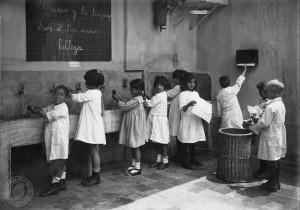Antes de sentarse a la mesa los niños se lavan las manos utilizando para secarsetoallas de papel como medida de higiene. Noviembre de 1921.documento Fotográfico. Inventario 14072. Archivo General de la Nación