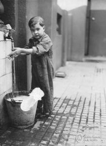 Niño lavándose las manos en un conventillo de La Boca, 1930