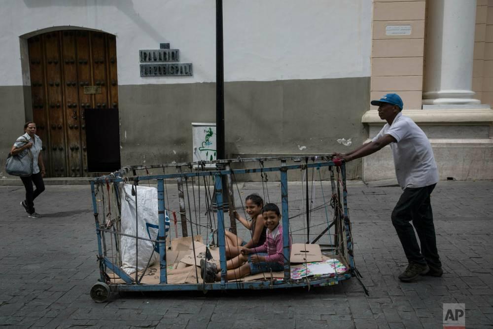 Un hombre traslada a sus hijos por el centro de Caracas en un carrito de reciclaje. 14 de mayo de 2019.