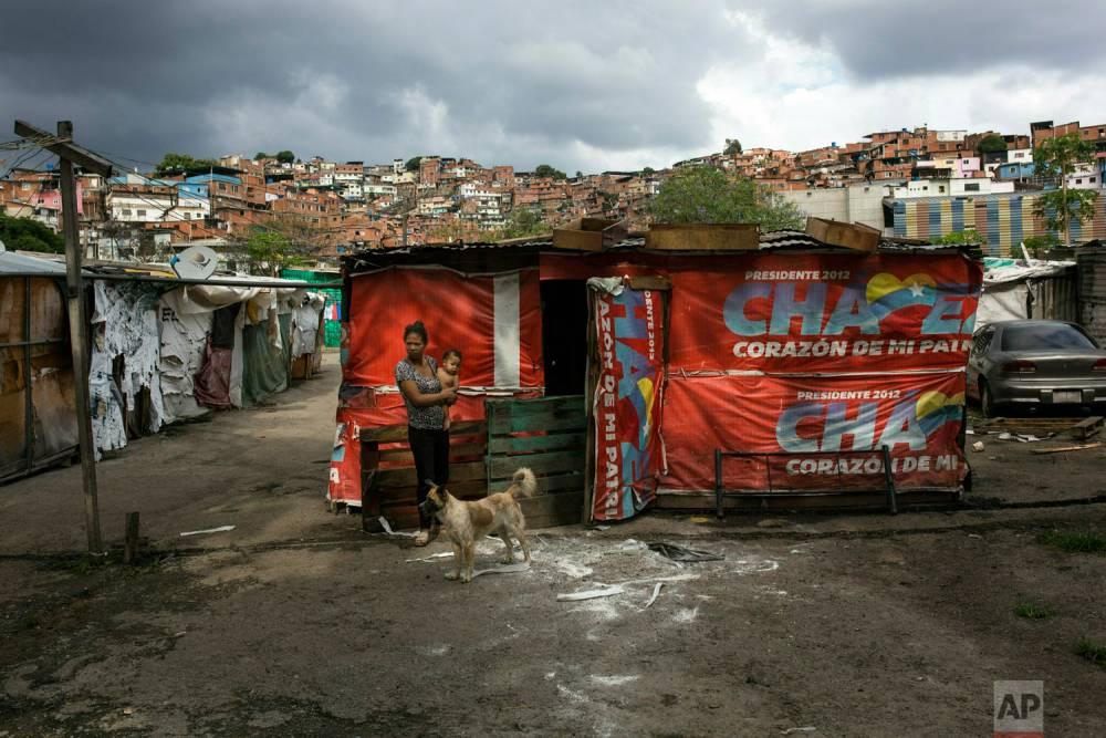 """Una mujer y su bebé frente a su choza en el barrio """"Siembra Socialista"""". Caracas, 9 de mayo de 2019."""