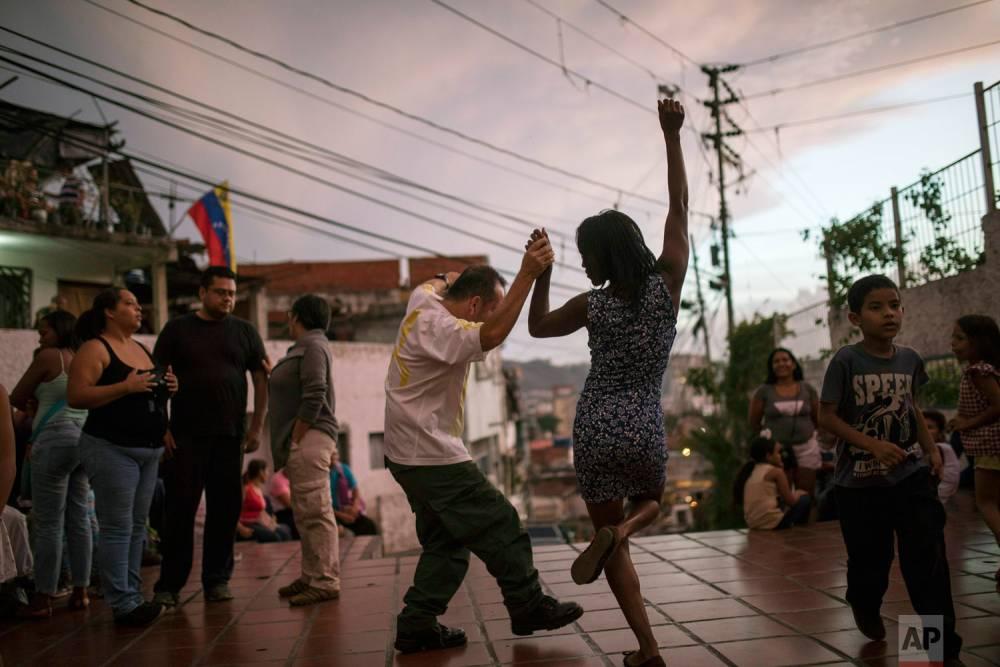 Irene Vaamondez, derecha, baila con un vecino mientras los músicos tocan en vivo en una plaza pública. Caracas, 11 de mayo de 2019.