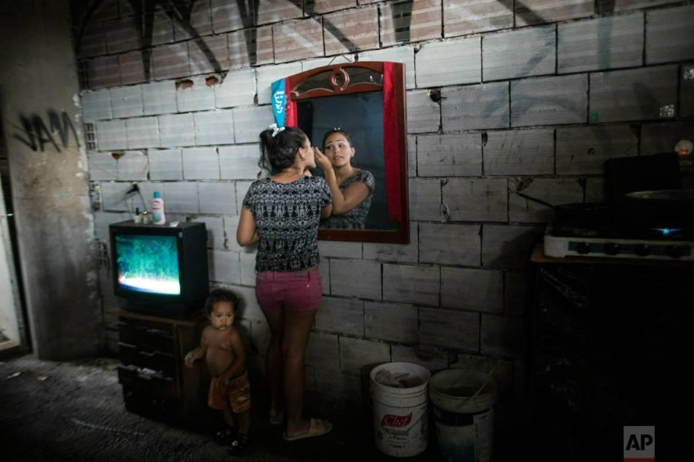 Adriana Rodríguez se maquilla en la habitación que comparte con sus tres hijos y siete miembros de otra familia, en un edificio ocupado. Caracas, 6 de mayo de 2019.