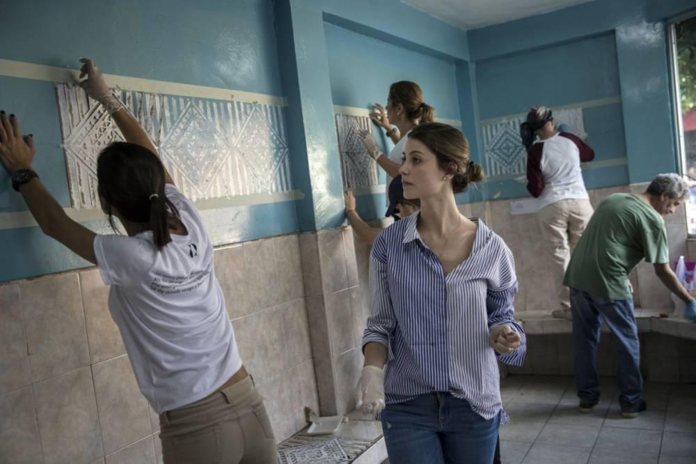 Stefanía Fernández observa el trabajo de invitados a su boda que aceptaron decorar una escuela antes de la ceremonia.