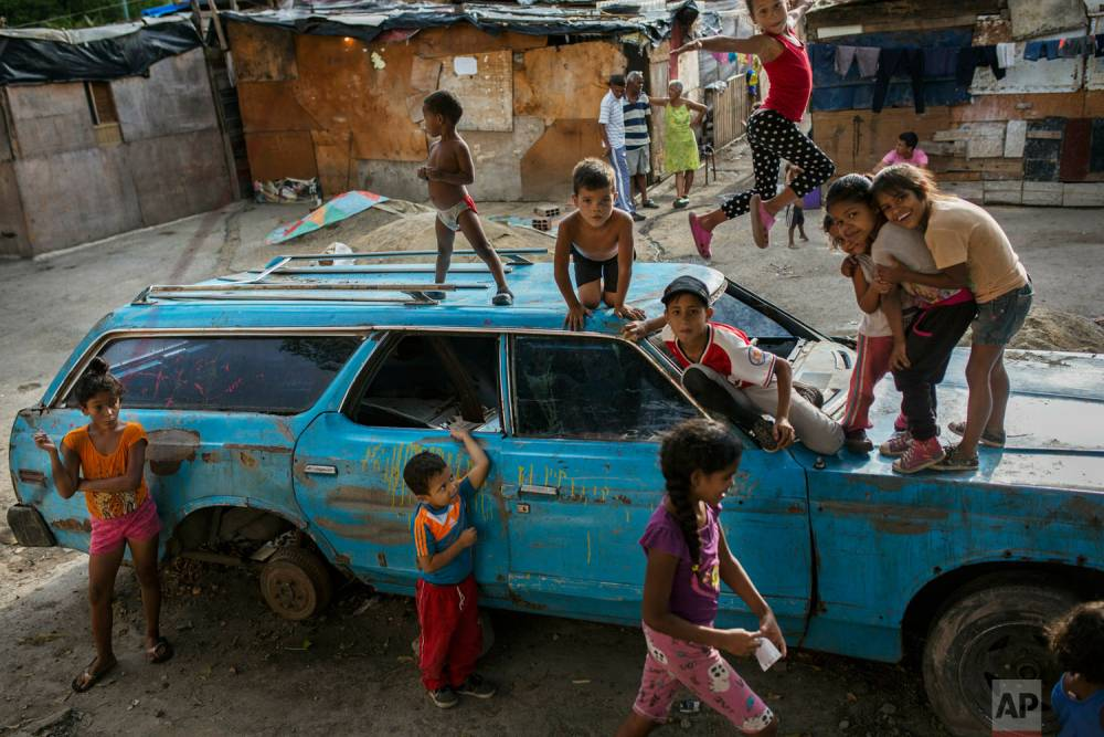 """Niños que juegan con un auto abandonado en el barrio """"Aguerridos Liberator"""". Caracas, 9 de mayo de 2019."""